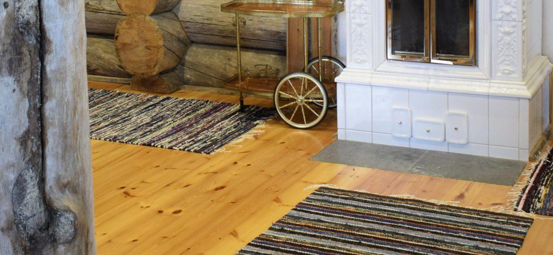 Kelolankuista valmistettu lattia, jolla on räsymattoja.